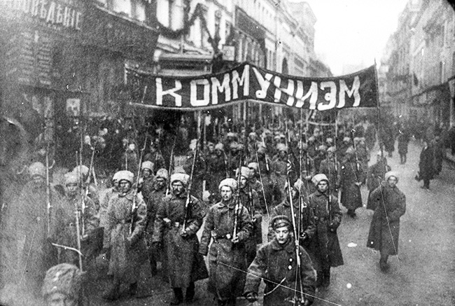 Armed soldiers carry a banner reading Communism Moscow Russia October 1917RESIZE